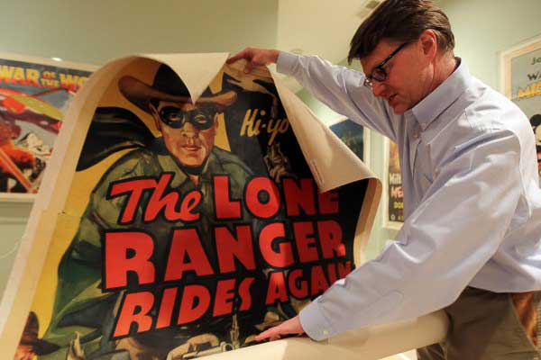 Dwight Cleveland unraveling a poster of from the film 'The Lone Ranger Rides Again'